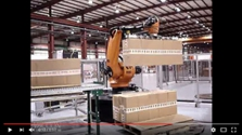 Vaccon robotic End-of-Arm tool on industrial robot palletizes corrugated boxes and slip sheets